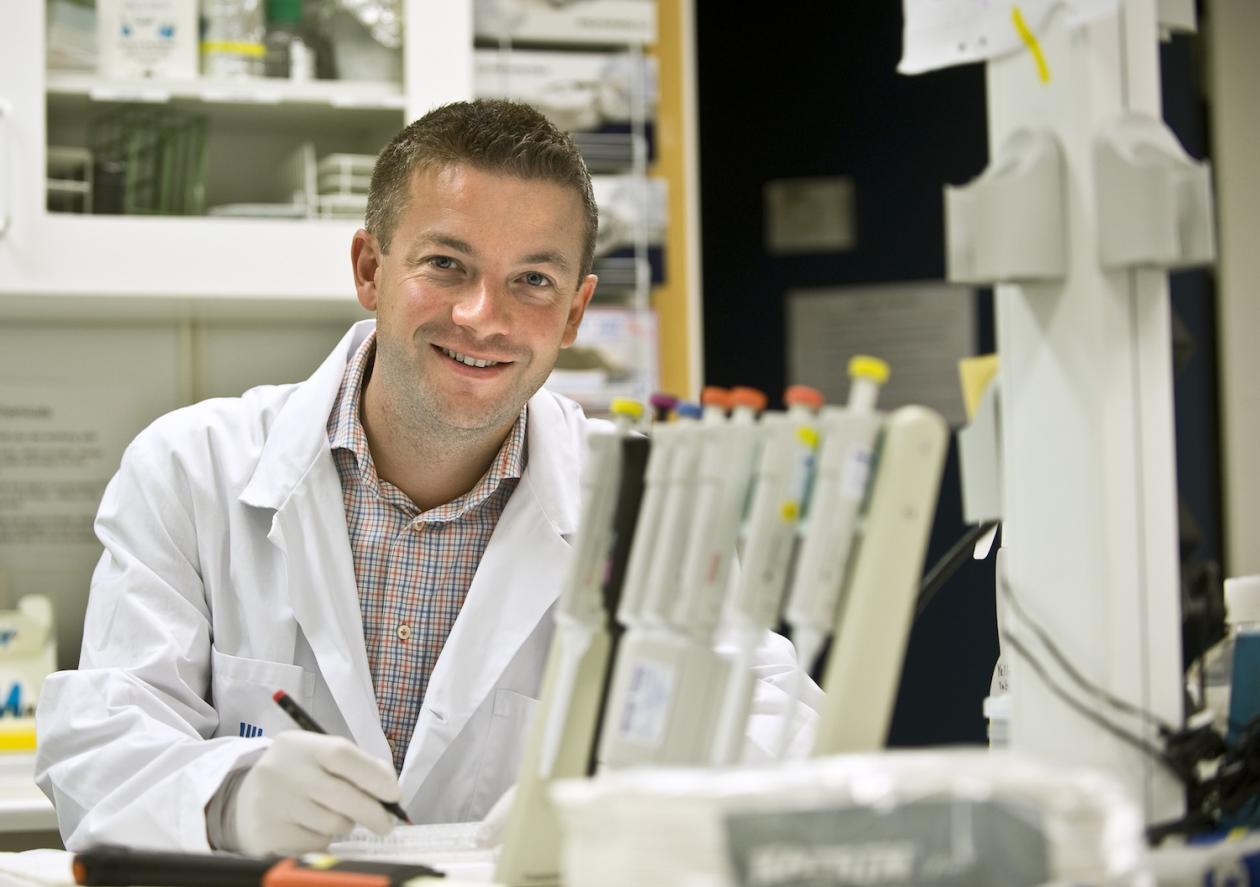 Yenan Bryceson på laboratoriet i hvit frakk, smilende mot kamera.