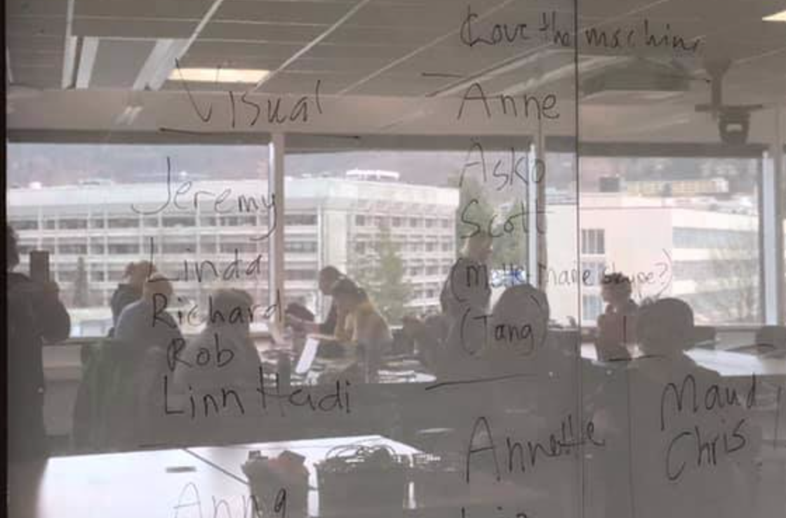 Photo of a wall with names written on it. In the shiny surface of the wall you can see the reflection of people sitting at tables, and a view of buildings seen out of large windows.