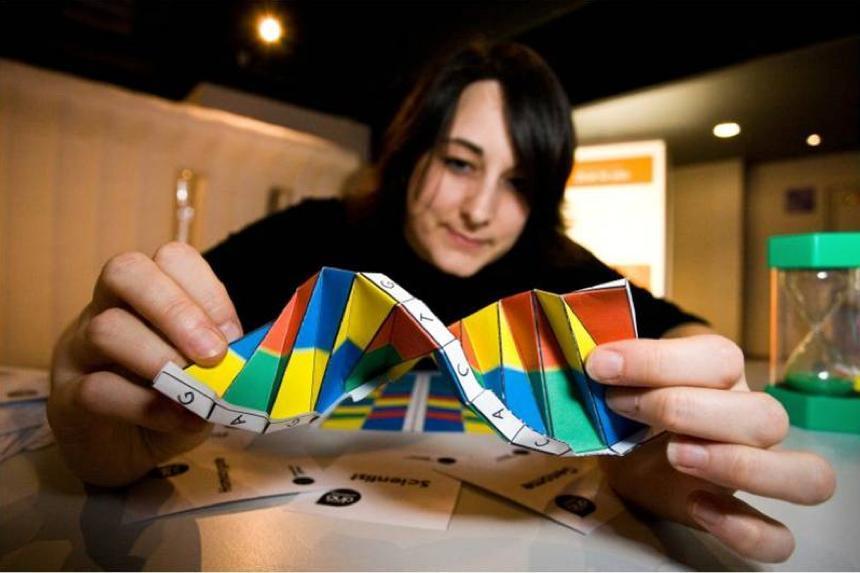 Mørkhåret ung kvinne med lys hud holder en DNA-figur laget av papir