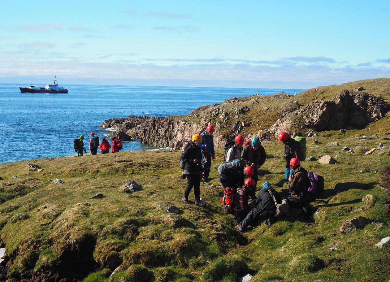 Students surveying the grassy vegetation on the coast of Svalbard with a ship on the sea in the background