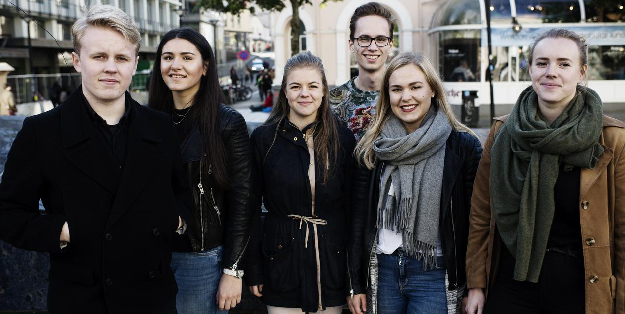 Seks studenter står ved den Blå steinen i Bergen sentrum