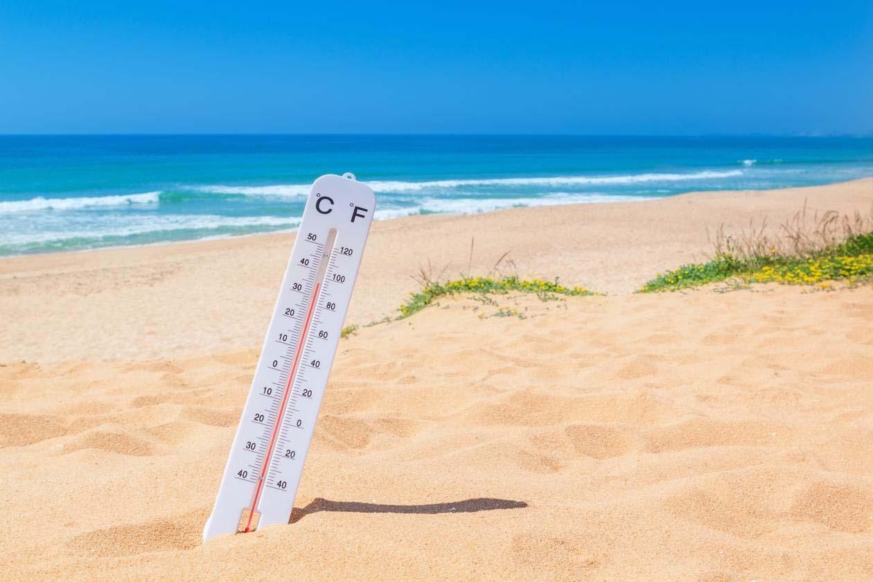 Thermometer stuck in the sand on a beach, showing scorching heat, image used to accompany an article on heat waves and climate change.