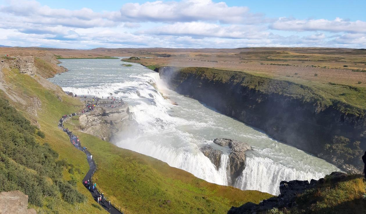Gigantic waterfall at Iceland, and people walking into a view plateau in the middle of it.