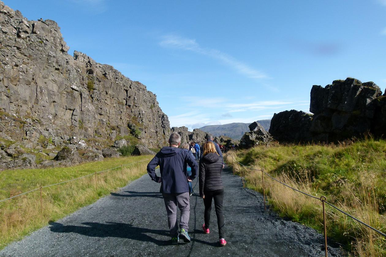 People walking and talking between huge cliff walls.
