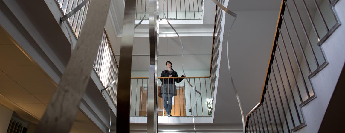 En kvinnelig student står stille i trappeoppgangen i Bjørn Christiansens hus