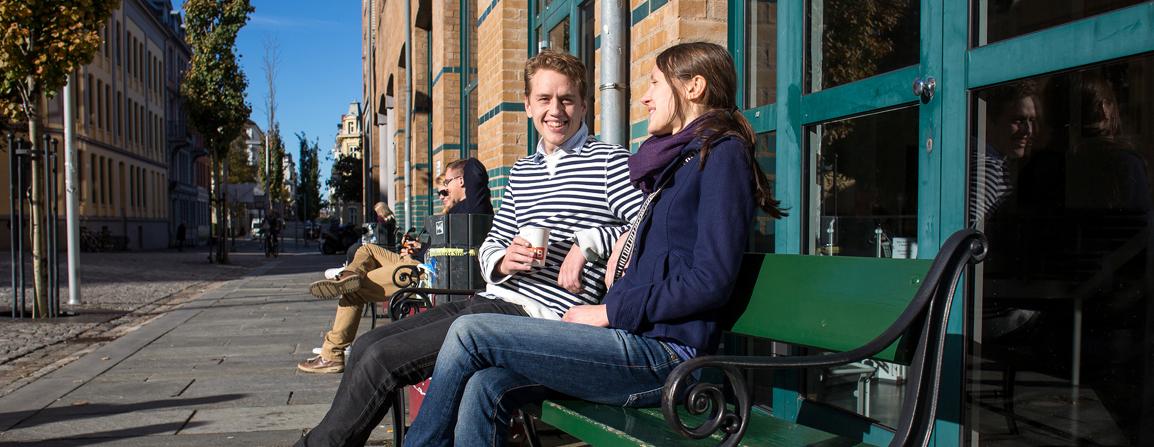 To studenter sitter utenfor SV-bygget og drikker kaffe i solen