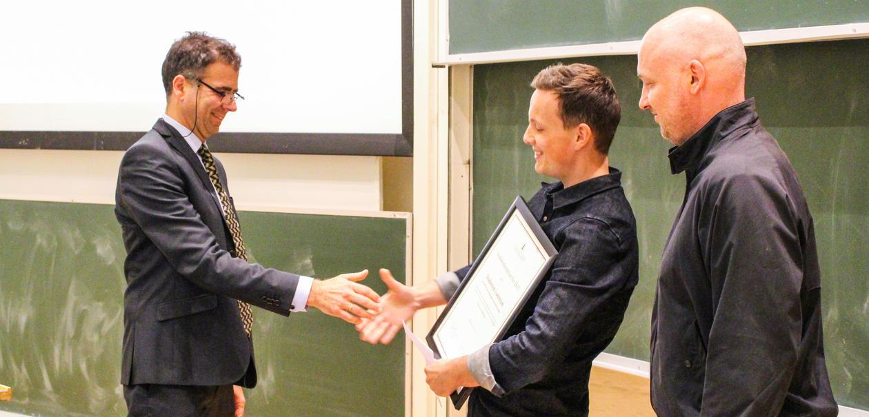 To smilende menn mottar et diplom fra visedekan for utdanning i Stort auditorium.