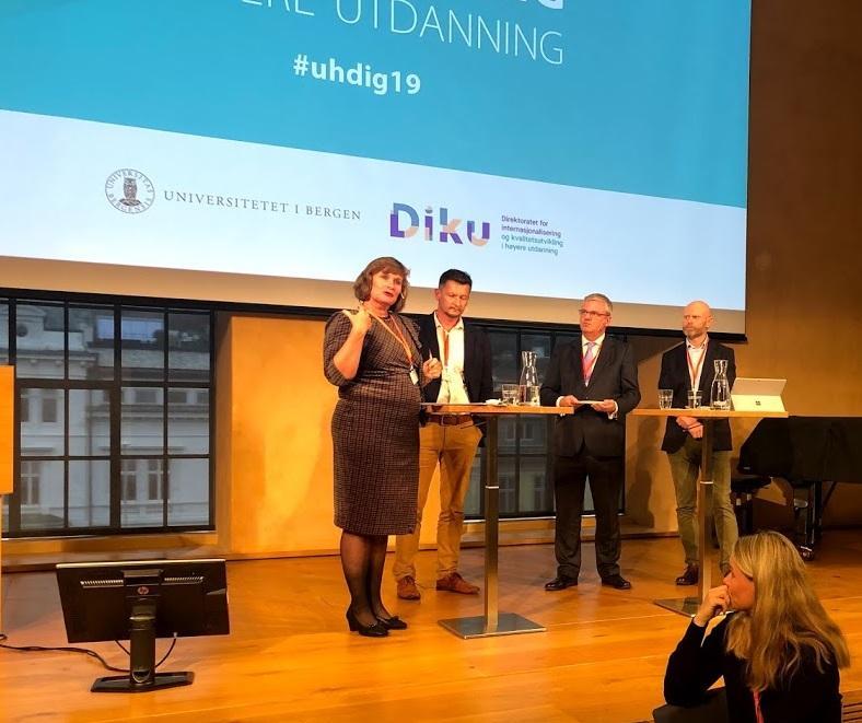 Panel på scenen i aulaen med Oddrun Samdal, Terje Mørland, Harald Nybølet og Roar Olsen.