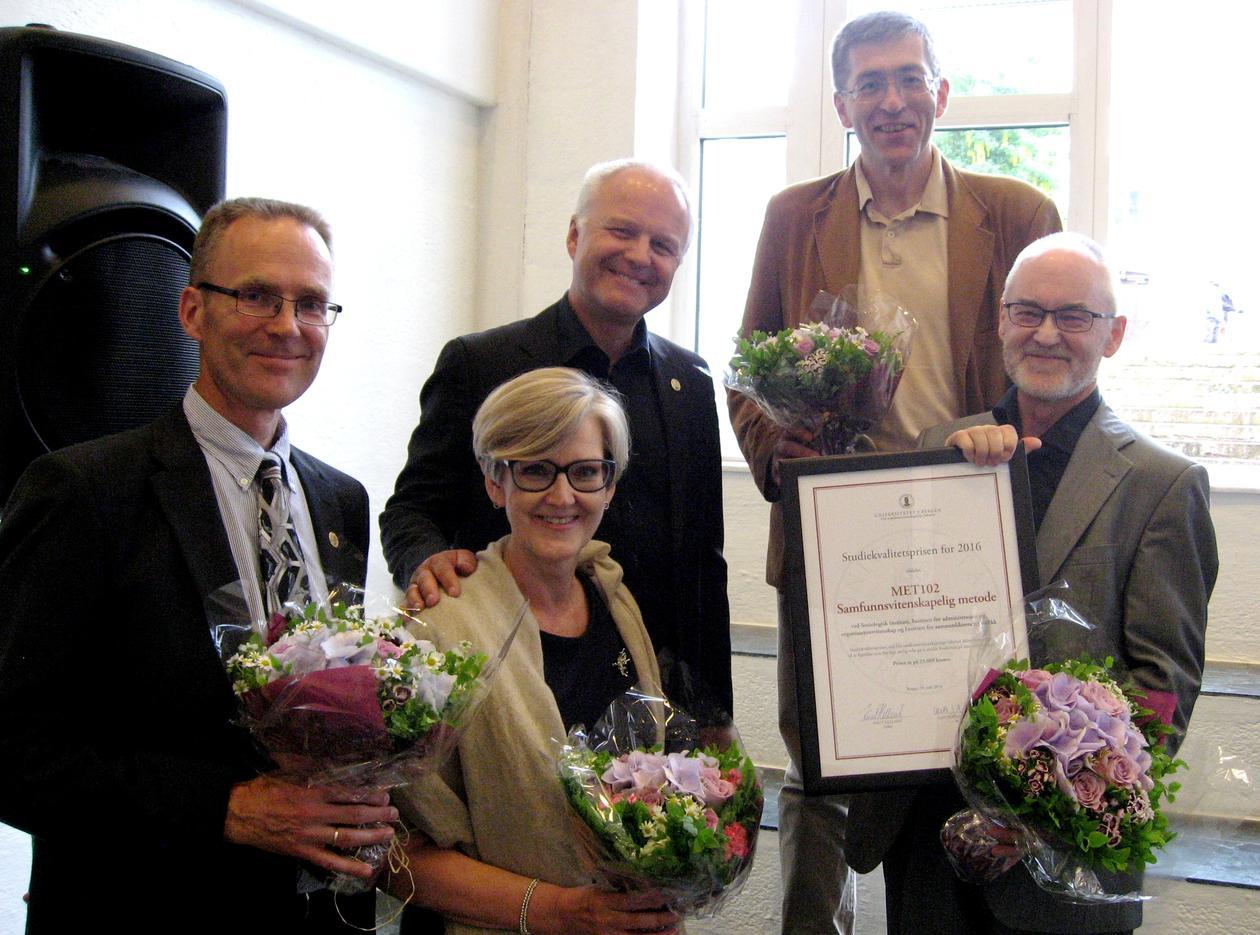 De fire mottakerne av Studiekvalitetsprisen og dekanen smiler mot kamera med blomster og diplom