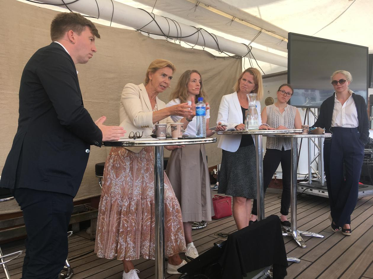 A passionate Kristin H. Holth speaking during a debate in Arendal, Norway on 14 August 2019  whilst (left to right) Inga Berre, Hege Økland, Ragnhild Freng Dale, and Hege Hammersland-White listen. Moderator Ole Øvretveit on far left.
