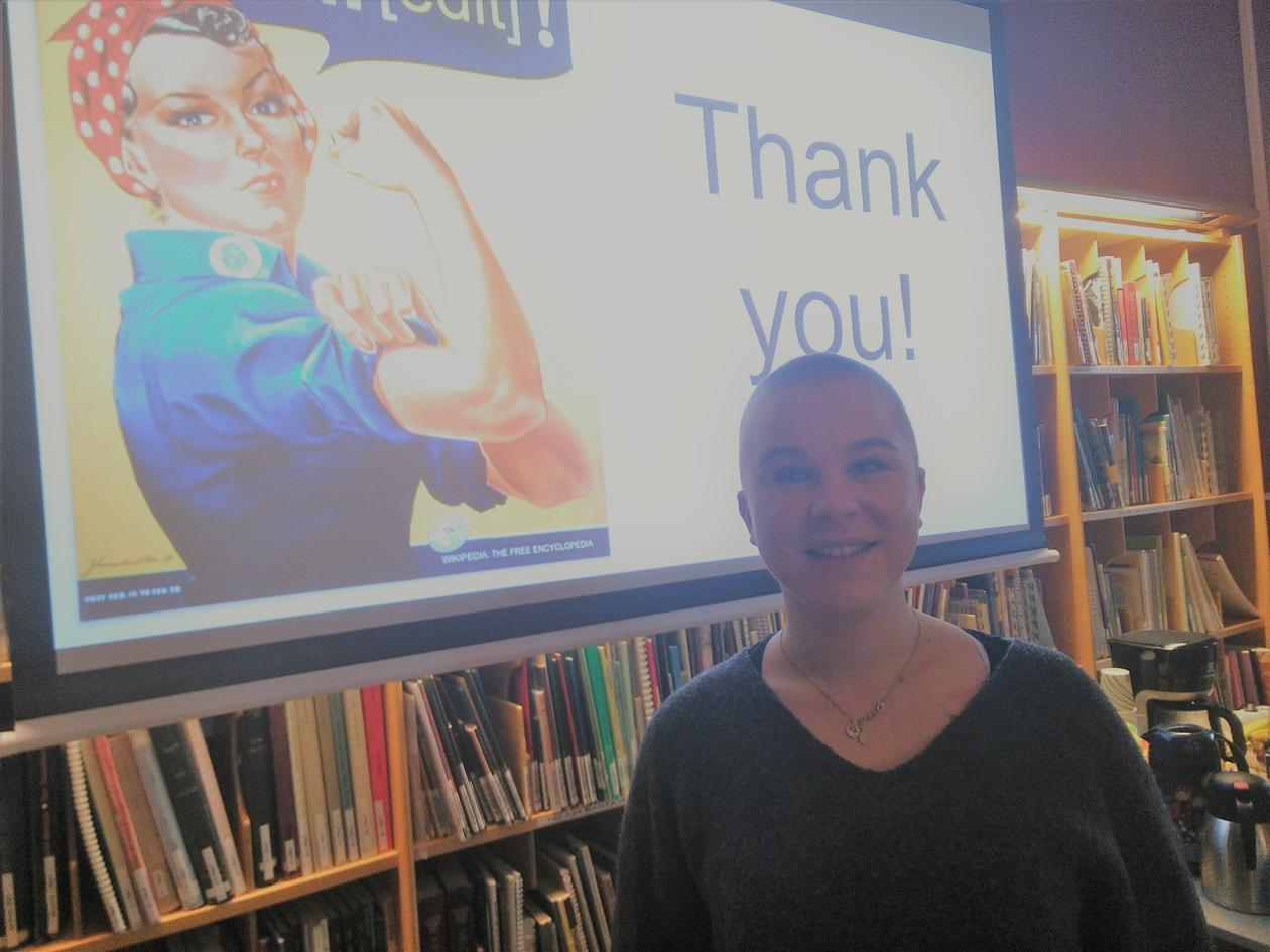 "photo showing the workshop leader Sabine Rønsen in front of the final powerpoint slide that has a picture of Rosie the Riveter saying ""we can [edit]!"" next to the text ""Thank you!"""