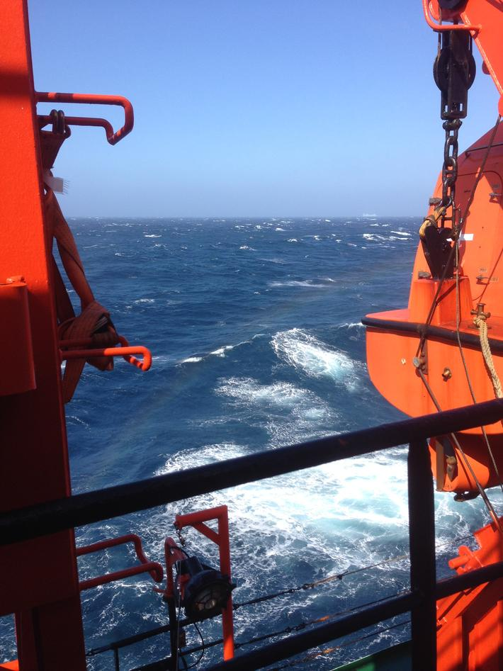View from a vessel towards blue sea with some white wave tops