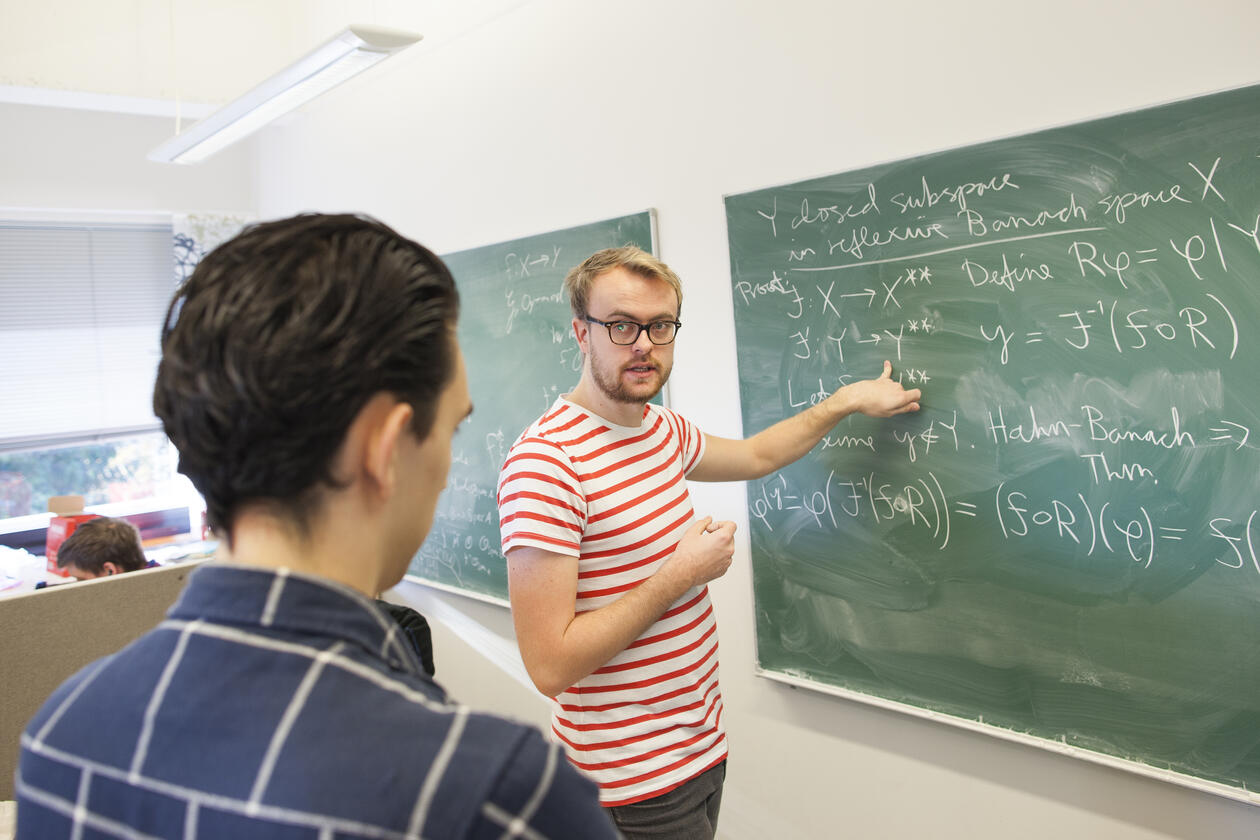 En student viser en annen student matematiske formler på en tavle