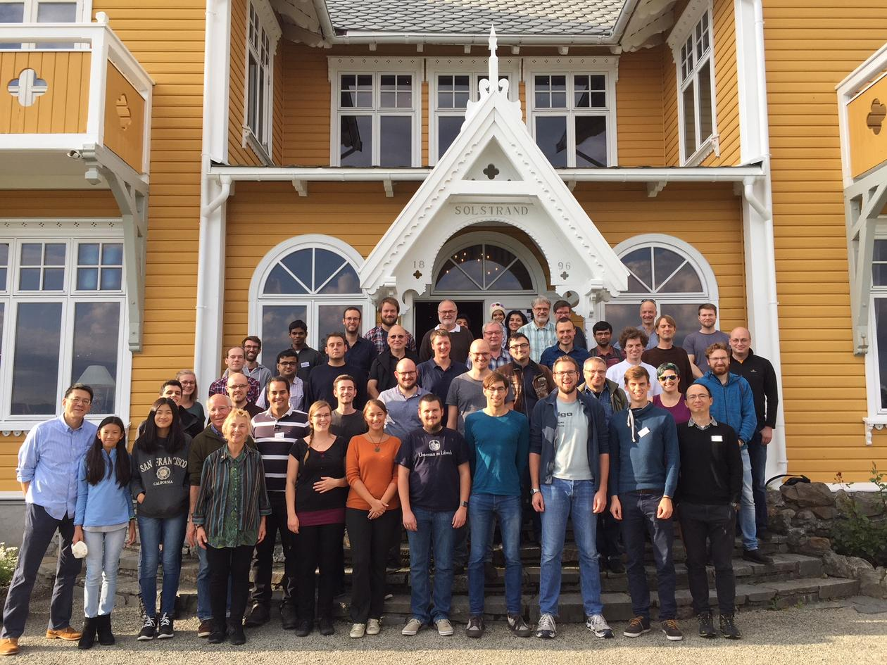 The image depicts the participants of the Operations Research and Parameterized Complexity Workshop, held at Solstrand Hotel, Bergen between 17 and 18 September 2018. The participants are grouped along a staircase with the hotel in the background.