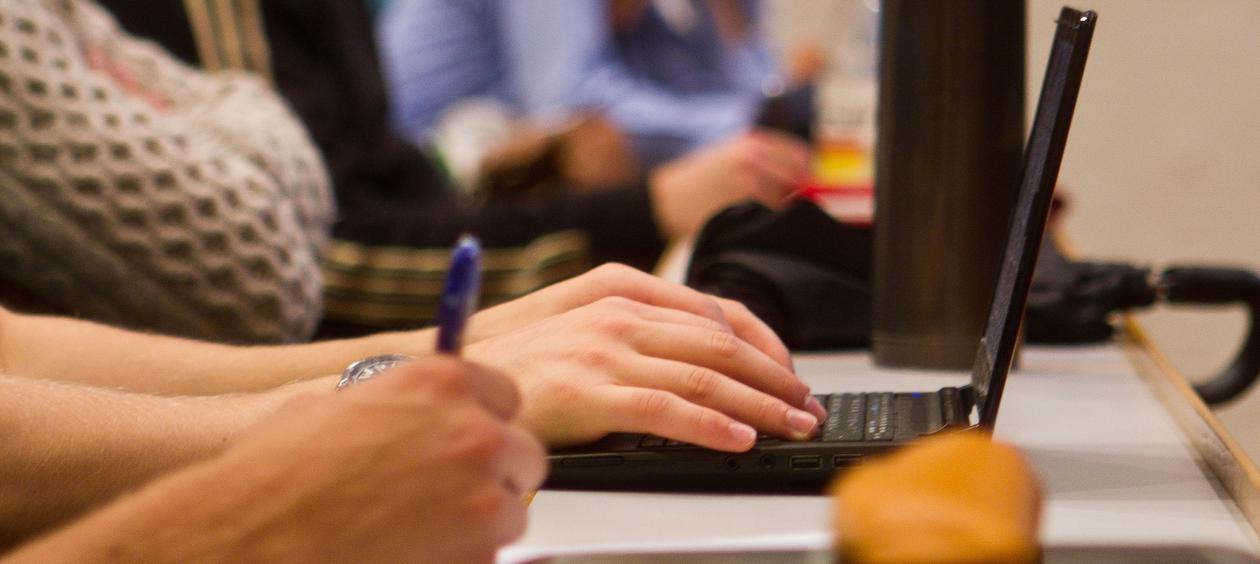 En student noterer på datamaskin under forelesning i Stort auditorium