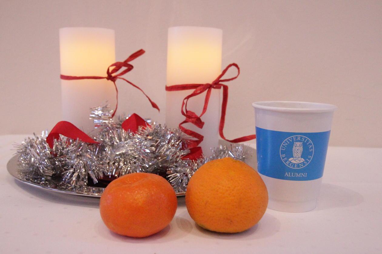 bilder av to stearinlys, mandariner og en UiB Alumni-kopp