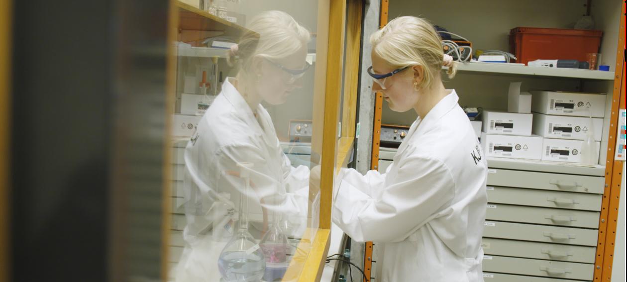 Bilde av en jente med vernebriller som blander kjemiske stoffer