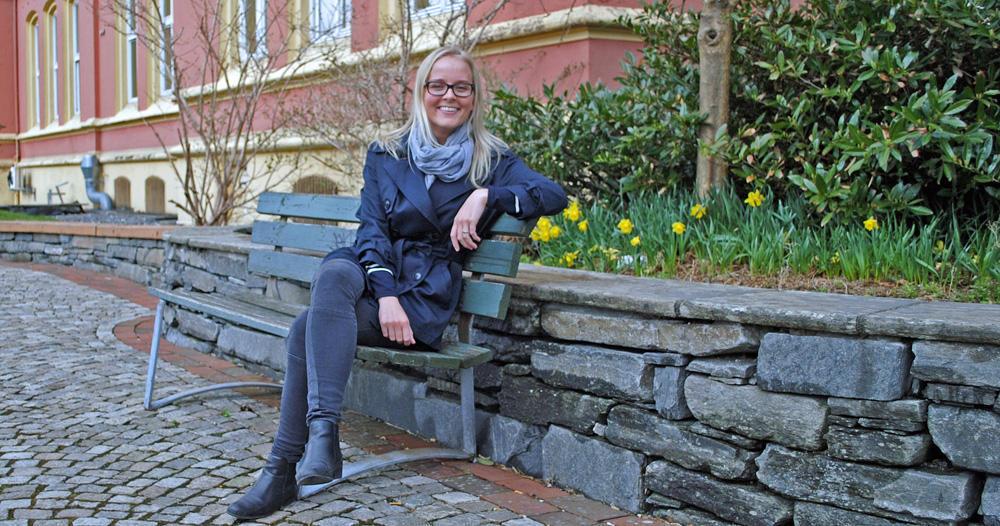 Ingrid sitter på en benk..