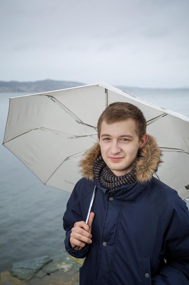 Aleksei outside with an umbrella