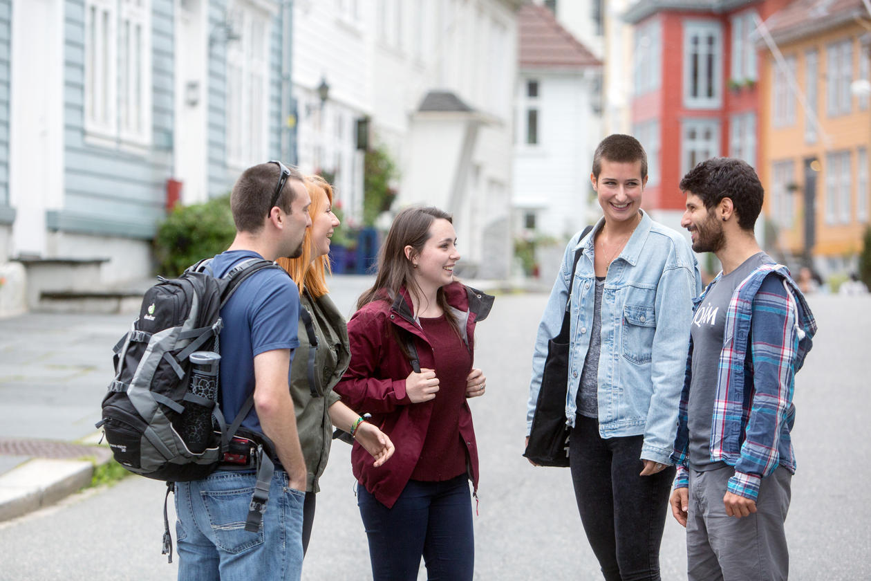 Five students in a group, talking, smiling