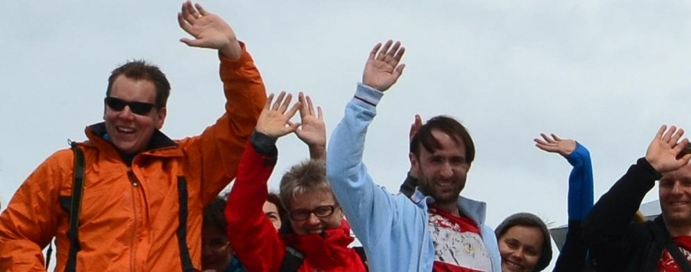 Five people waving and smiling