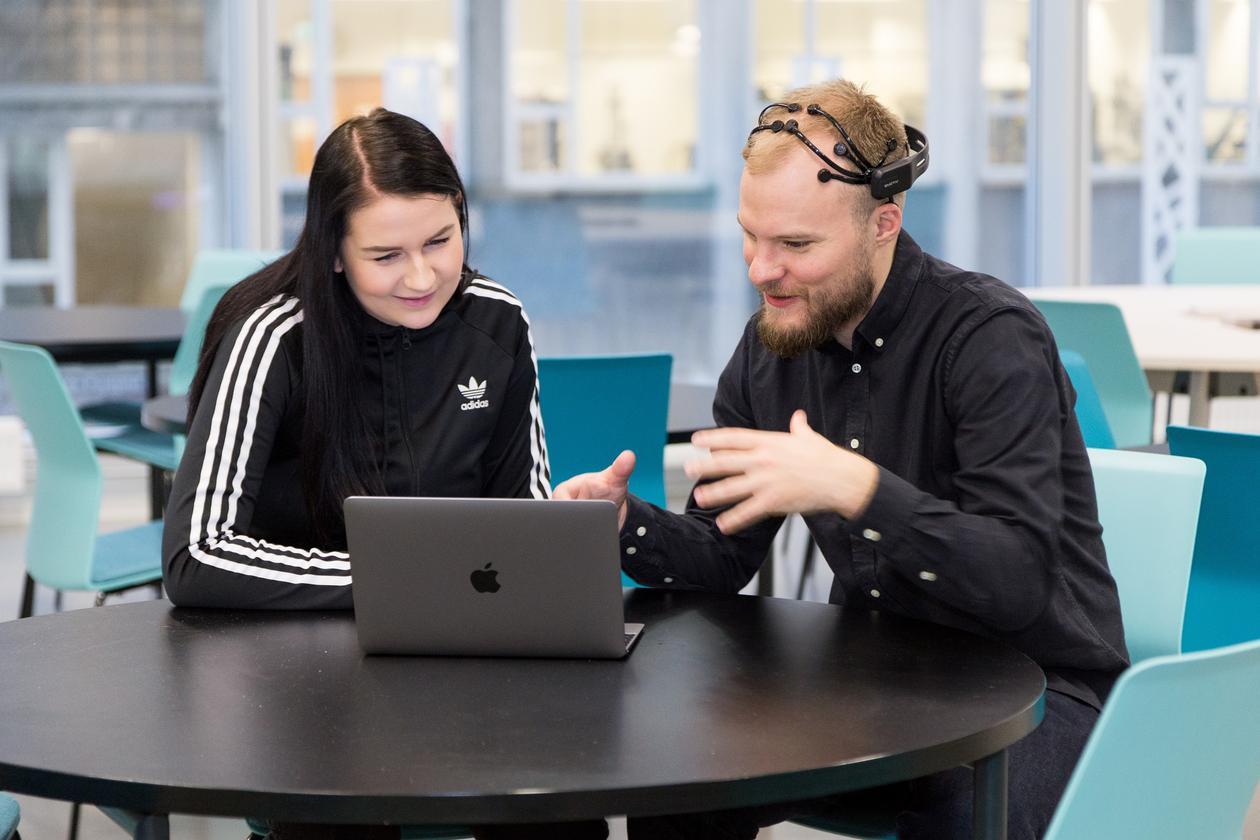 IT-utdanning: Bildet viser to studenter som sitter ved et bord og ser på en laptop og prater.