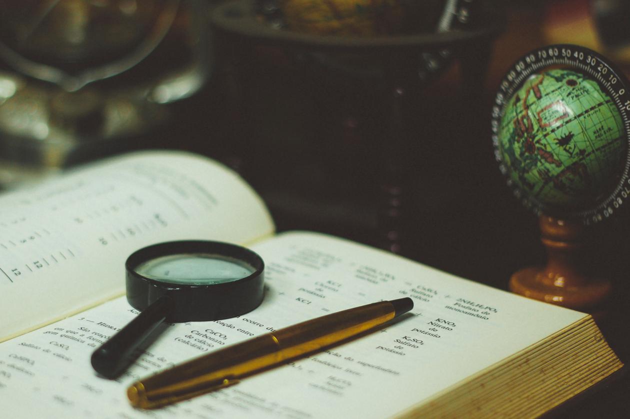 Forstørrelsesglass, penn, bok.