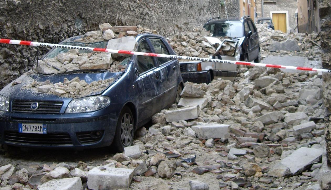 Cars devastated by rubble in one of the streets of the Apennines in Italy after the deadly earthquake of 2009.