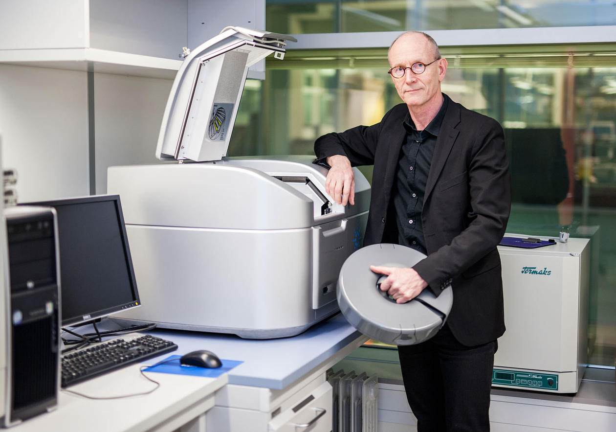 Professor Kalland standing in front of the micro matrix machine in the lab.