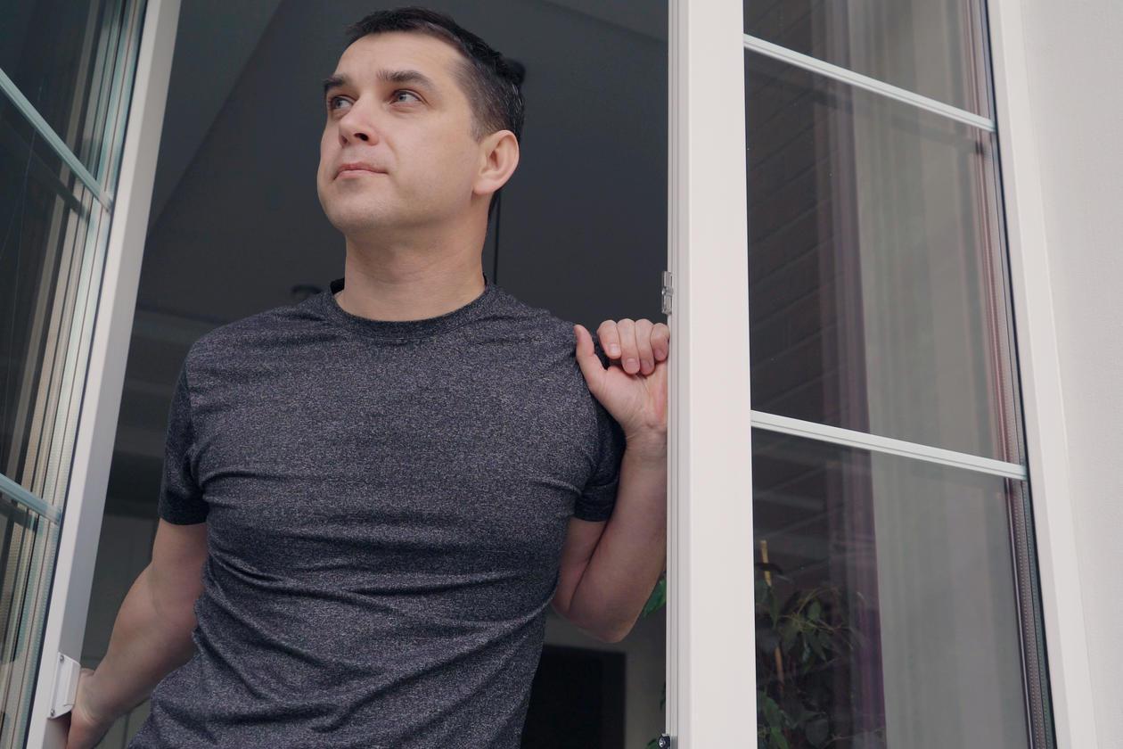 Man standing in the doorway looking out