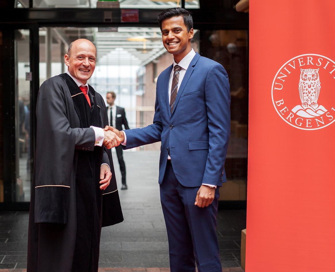 Studenttaler Sananthan Gunaratnam hilser på dekan Karl Harald Søvig