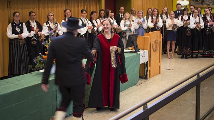 Dekan Nina Langeland handhelser på dei nyutdanna