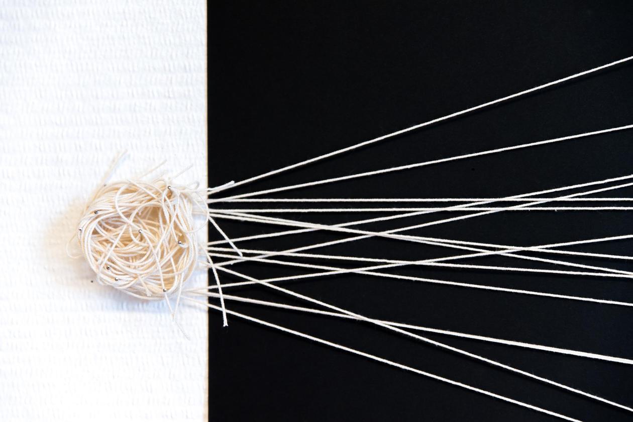 Bilde av mange tråder som trekkes ut fra en trådfloke, mot svart og hvitt bakgrunn