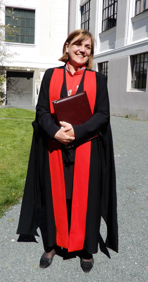 Kathy Willis dressed in her Oxford academic gown standing in the museum garden after receiving her honorary doctorate from University of Bergen
