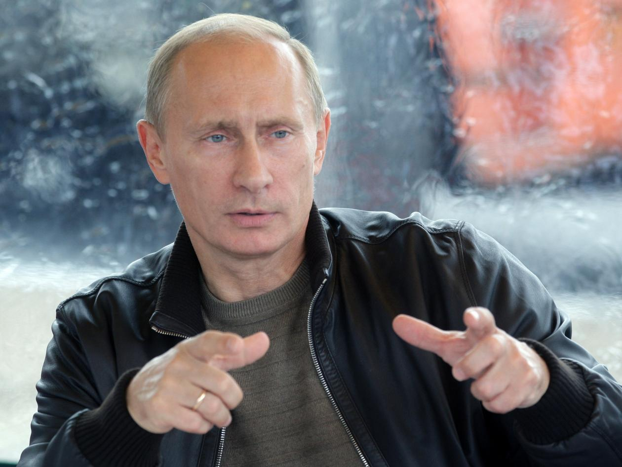 Picture of Russian President Vladimir Putin with hands raised forward and both forefingers pointed forwards.
