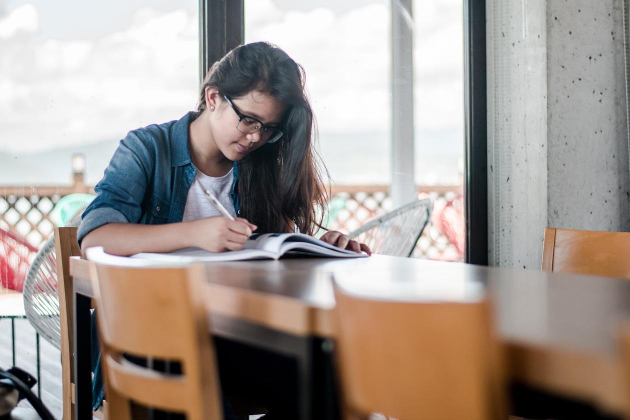 En kvinne som studerer ved et bord