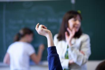 En elev rekker opp hånden, mens en annen skriver på tavlen i bakgrunnen.