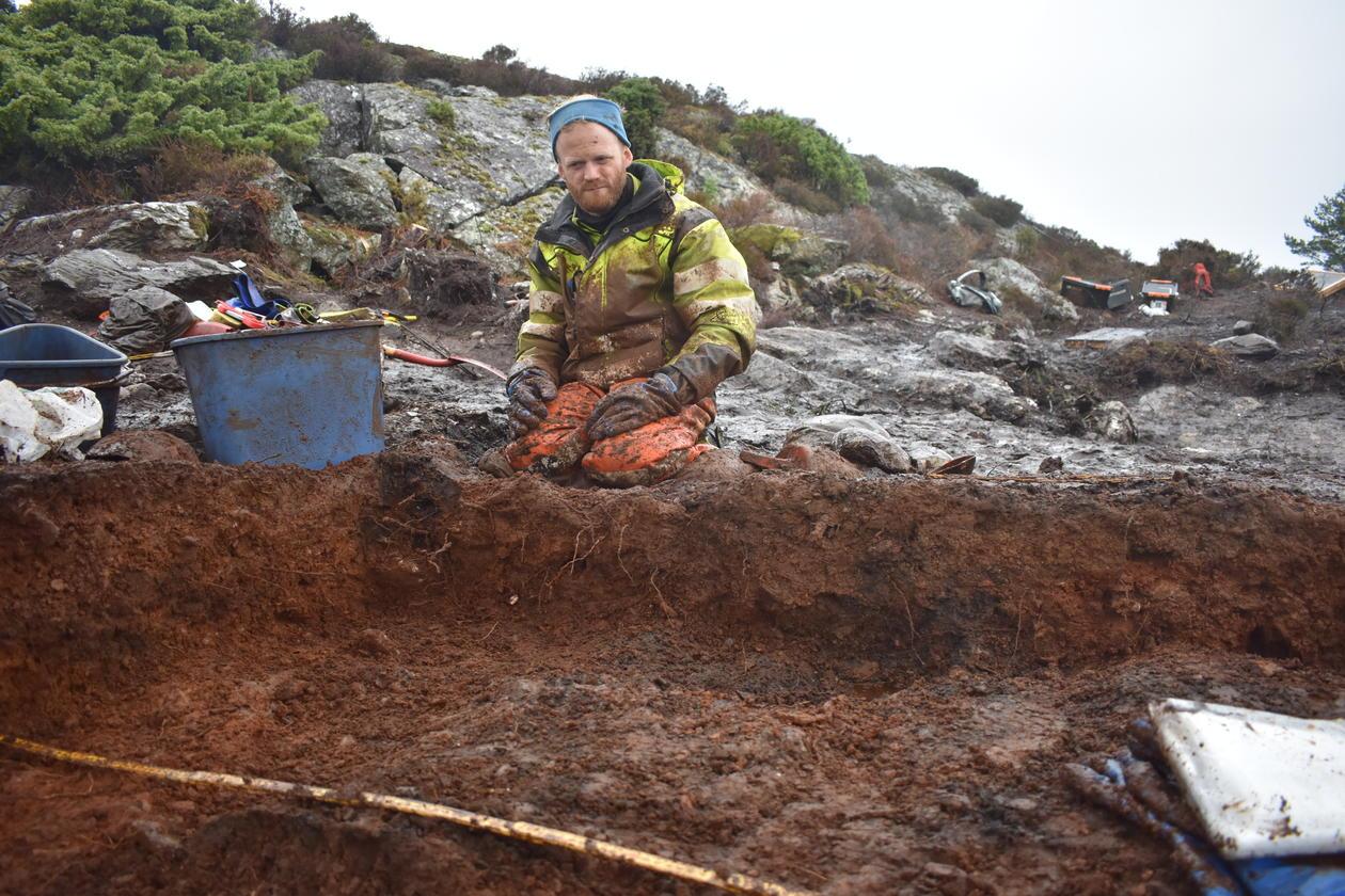 Bilde av arkeolog Lars Røgenes i felt, gjørmete
