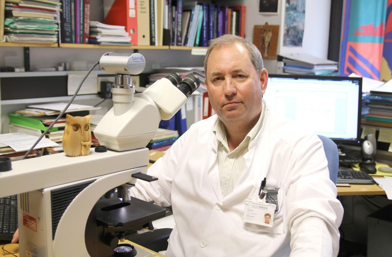 Lars Akslen med mikroskop på sitt kontor