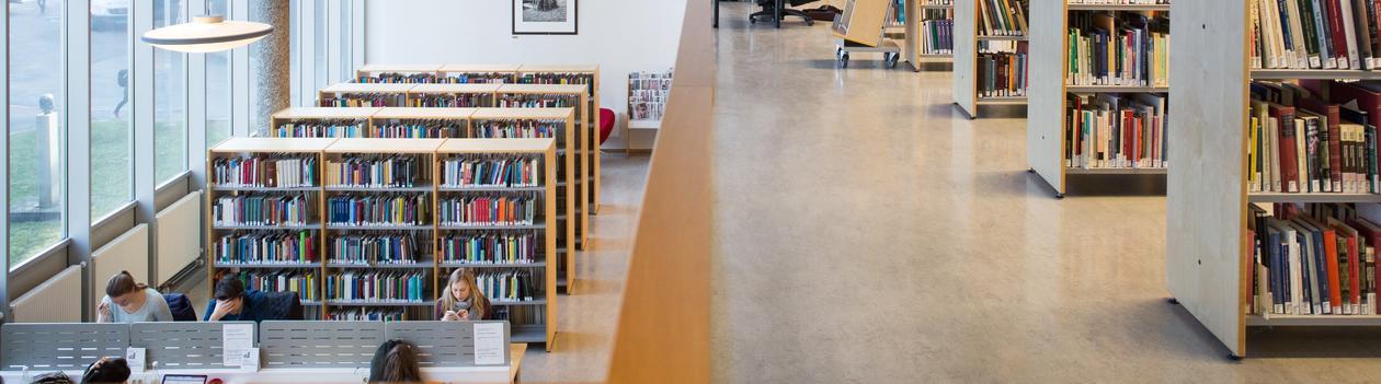 Oversiktsbilde fra et bibliotek med bokhyller og studenter som sitter og leser