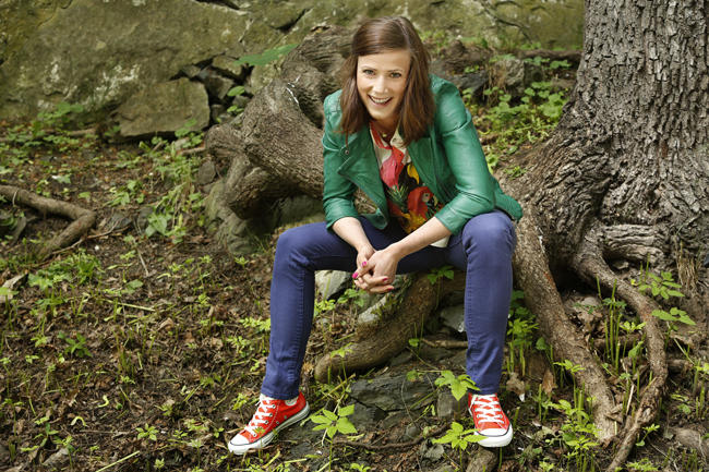 Line Jansrud sitter på en trerot i fargerike klær og smiler mot kameraet.