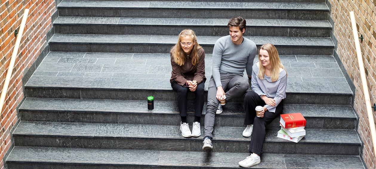 Tre studenter sitter i trappen på Jussbygget