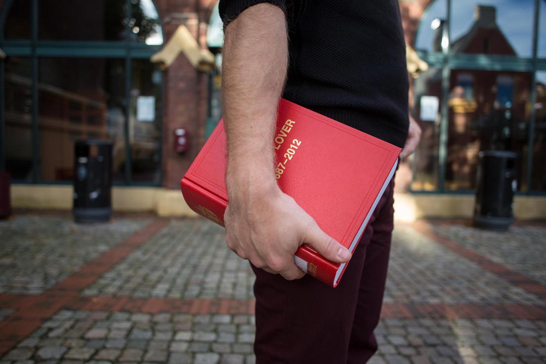 En student holder en lovsamling under armen.