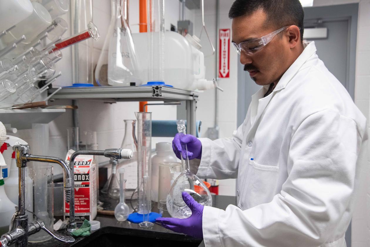 Mann i frakk med kjemiske prøver