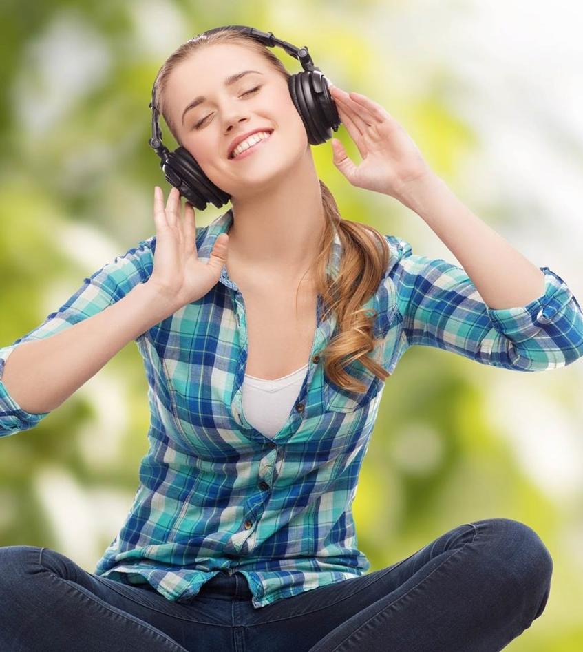 Glad jente som lytter med øretelefonen