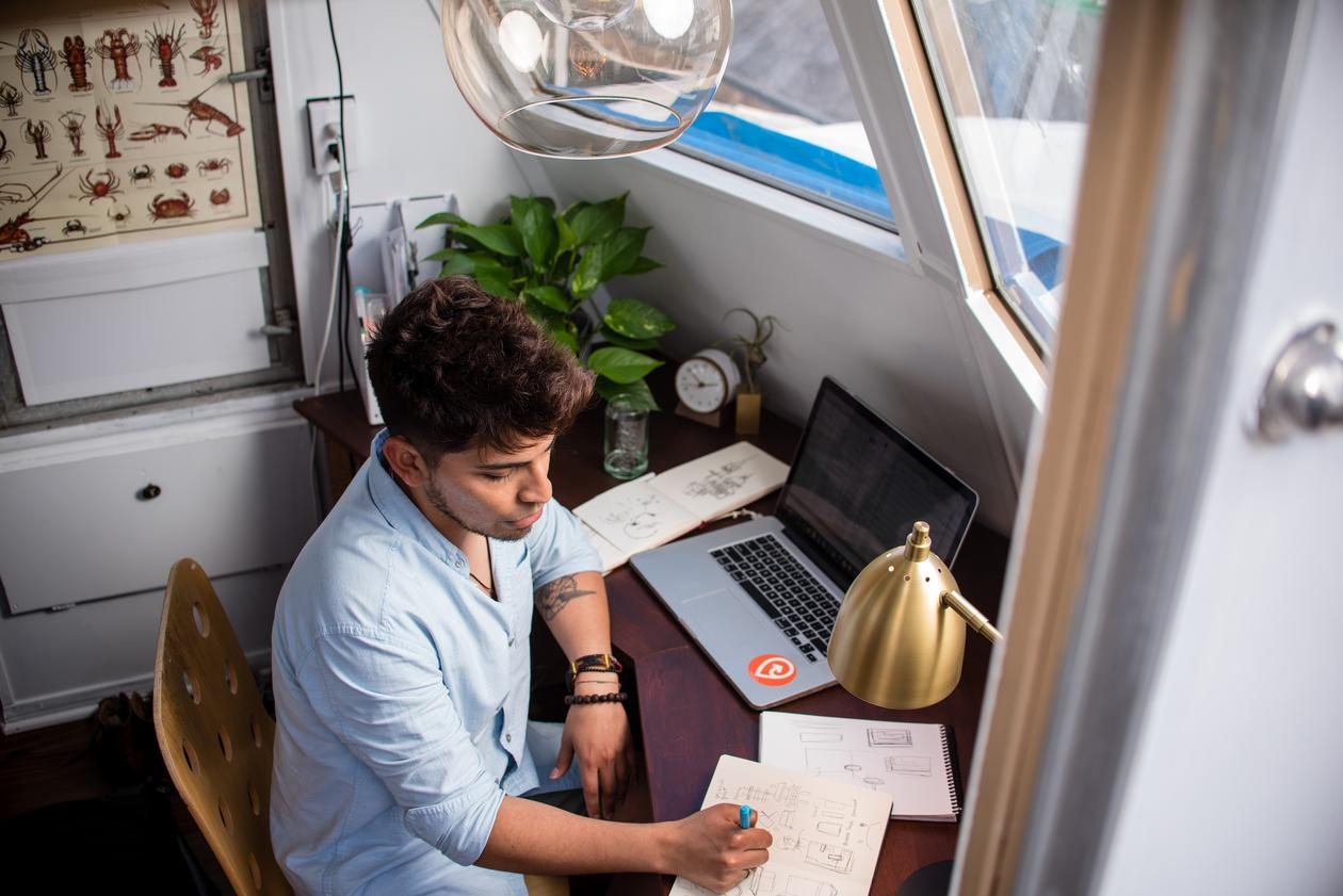 Student som sitter foran en laptop og jobber med skoleeksamen - hjemme