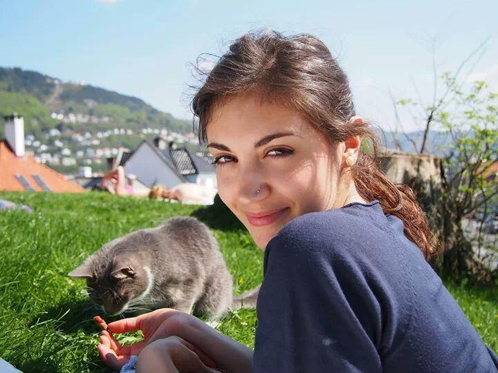 Photo of Martina and a grey cat enjoying the sun on a lawn at Klosteret in central Bergen