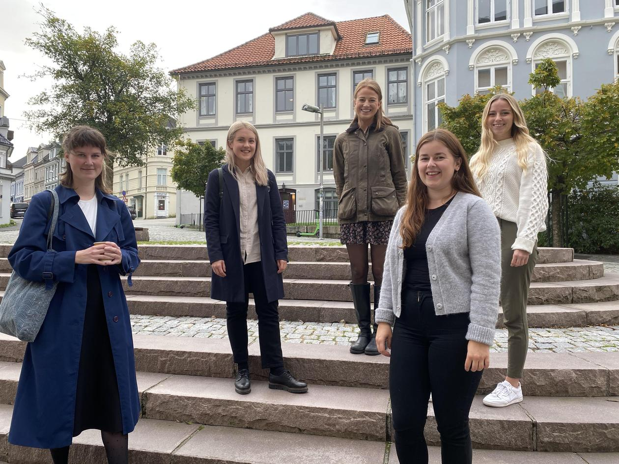 5 young women standing outside old buildings