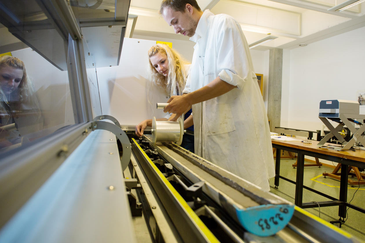 picture of researches putting plastic film on sediment core