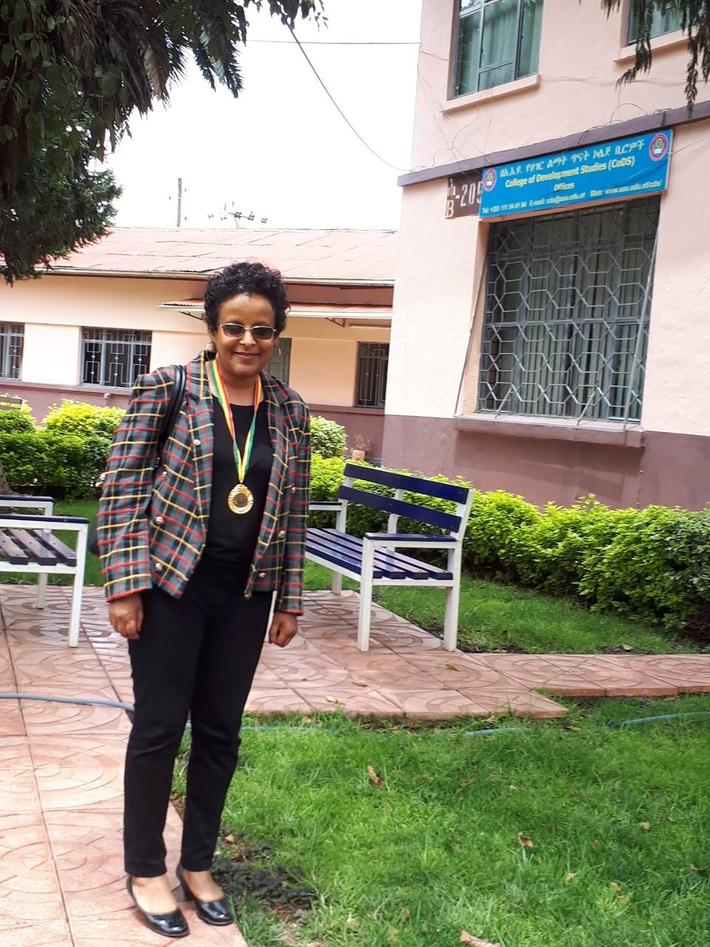 Mulumebet Zenebe standing in front of a building, wearing her medal